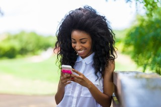 Outdoor Portrait Of A Teenage Black Girl Using A Mobile Phone -
